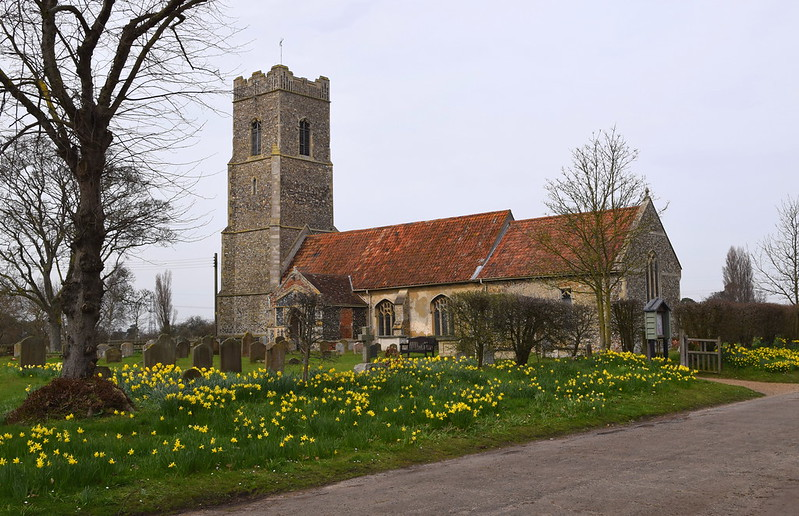 Snape Church showing the daffodils by the car-park
